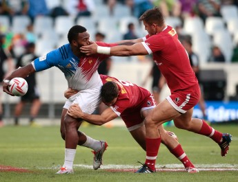 France's Virimi Vakatawa (L) is tackled by Canada's Justin Douglas (C) during the second round of the World Series Sevens rugby match at the Cape Town stadium in Cape Town on December 12, 2015. / AFP / GIANLUIGI GUERCIA        (Photo credit should read GIANLUIGI GUERCIA/AFP/Getty Images)